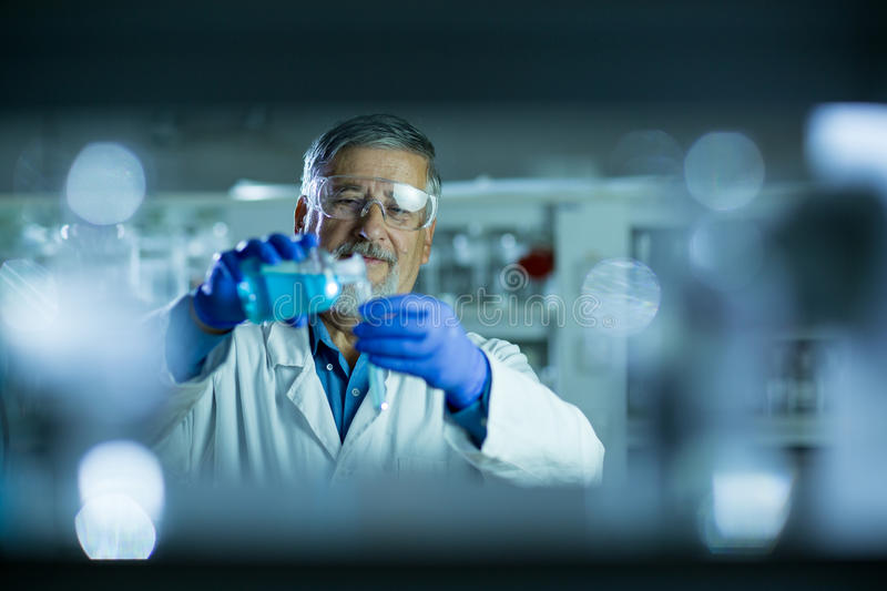 Senior male researcher carrying out scientific research in a lab. Shallow DOF; color toned image stock images