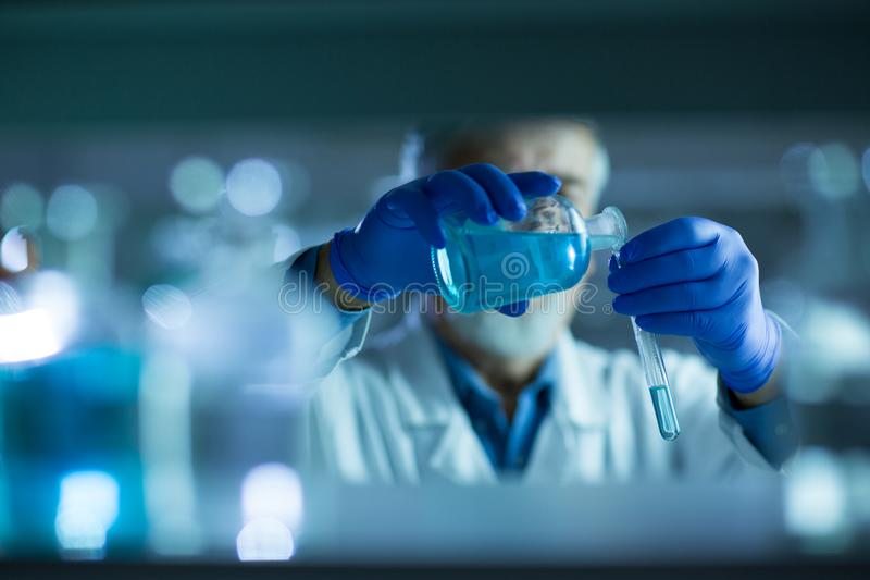 Senior male researcher carrying out scientific research in a lab. Shallow DOF; color toned image stock photography