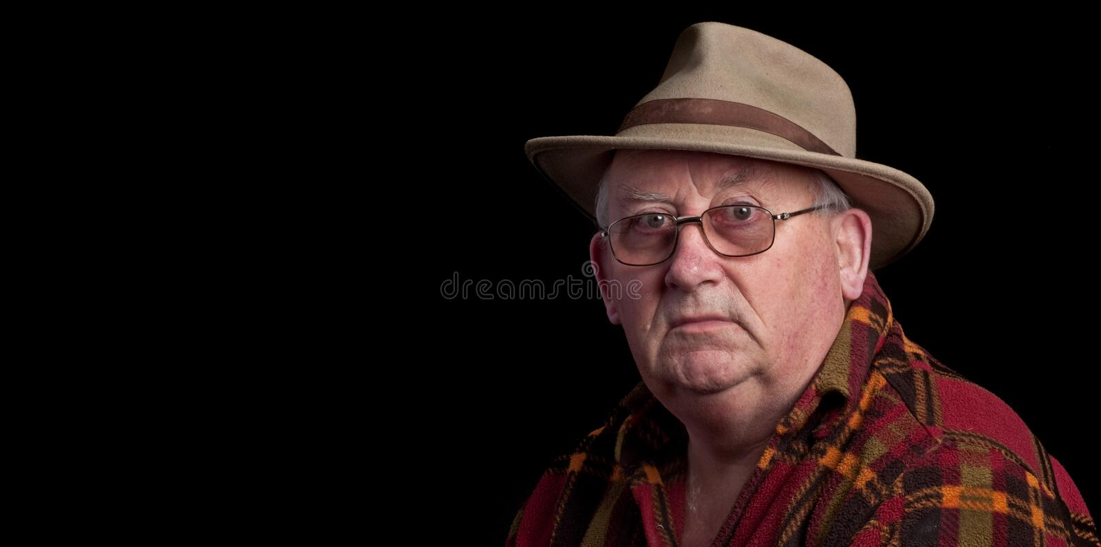 Senior male retired wearing glasses and hat royalty free stock photo