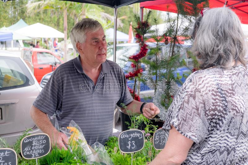 Senior male serving female customer at farmers market stall for royalty free stock images