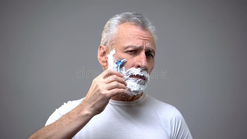 Senior male shaving, aging skincare cream, morning routine rituals, tradition. Stock photo stock photos
