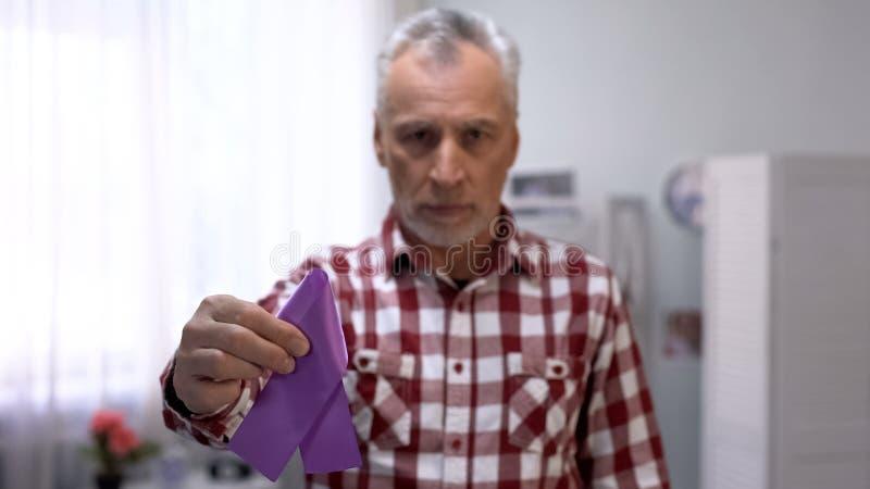 Senior male showing purple ribbon to camera, Alzheimer disease awareness, care. Stock photo stock image
