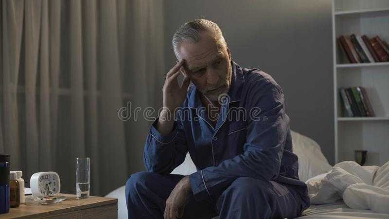Senior male sitting in bed and suffering from terrible headache at night stock photography