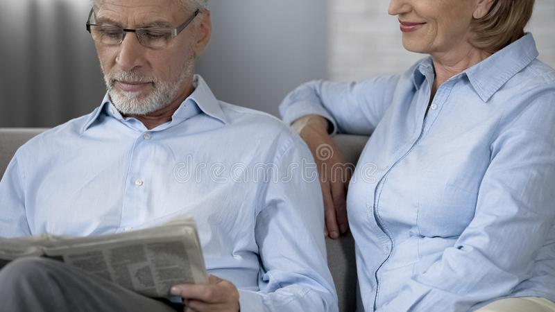 Senior male sitting on sofa reading newspaper, woman beside smiling, care royalty free stock photography