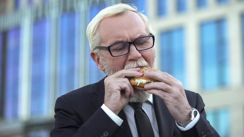 Senior male in suit eating burger during lunchtime, standing near office center stock photo