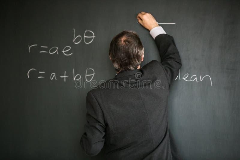 Senior male teacher teaching mathematics. Writing on the blackboard royalty free stock photos