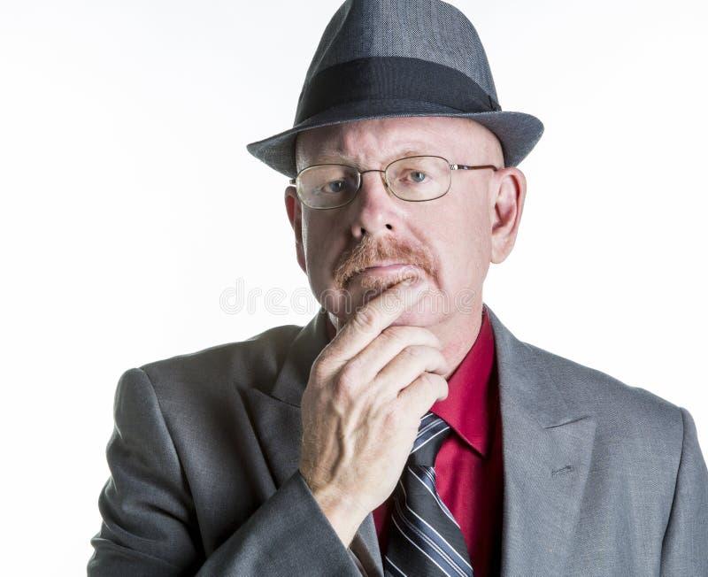 Senior Male thinking or Observing. Senior male in a suite and hate thinking or observing isolated on white stock photo