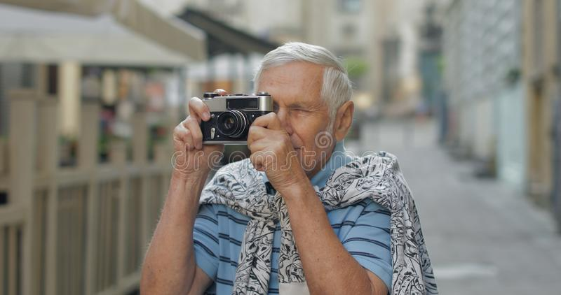 Senior male tourist exploring town and makes a photo with retro photo camera stock image