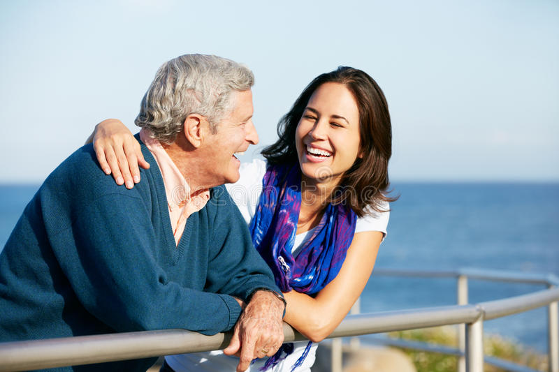 Senior Man With Adult Daughter Looking At Sea Stock Photo