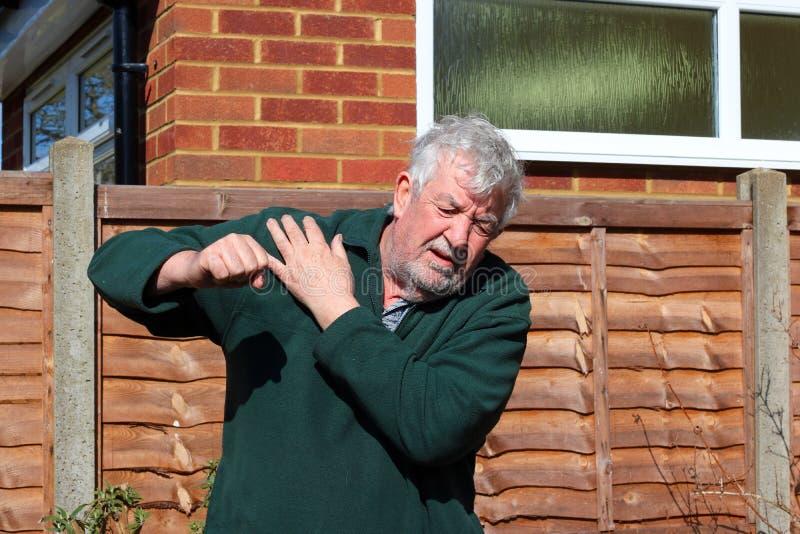 Senior man holding painful shoulder. A senior man in agony holding his painful shoulder. Either injured or arthritis stock images