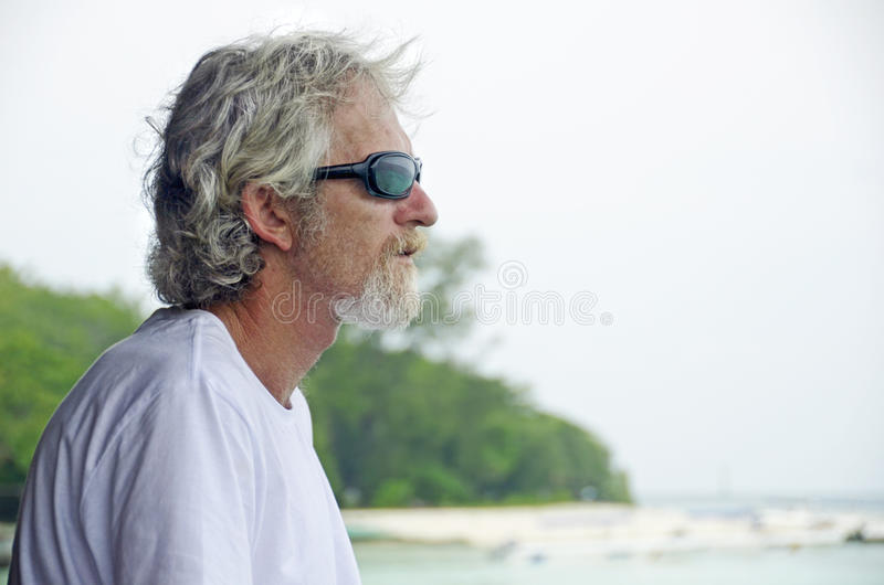 Senior man alone feeling emotional & thoughtful looking at ocean royalty free stock photo