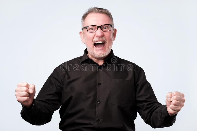Senior man is angry and mad raising fist frustrated and furious royalty free stock image