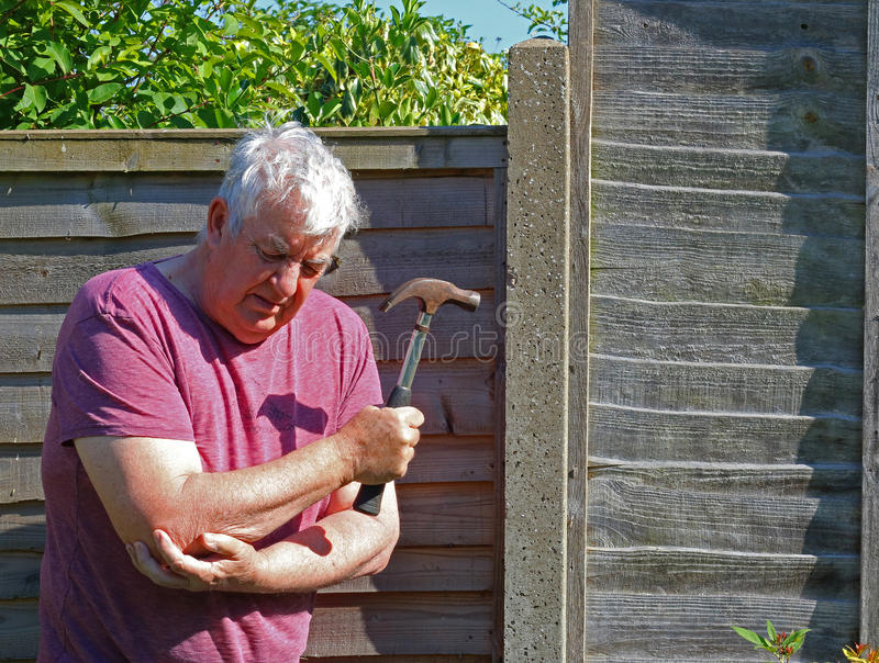 Senior man arthritis elbow. A senior man holding his elbow because of pain caused by arthritis or injury by using a hammer to repair a fence royalty free stock photography
