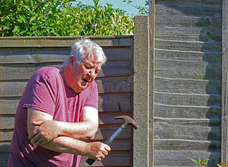 Senior man arthritis elbow. A senior man holding his elbow because of pain caused by arthritis or injury by using a hammer to repair a fence royalty free stock images