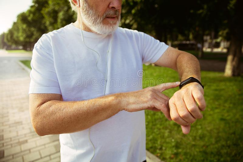 Senior man as runner with armband or fitness tracker at the city`s street royalty free stock photos