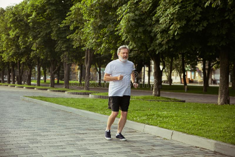 Senior man as runner with armband or fitness tracker at the city`s street royalty free stock image