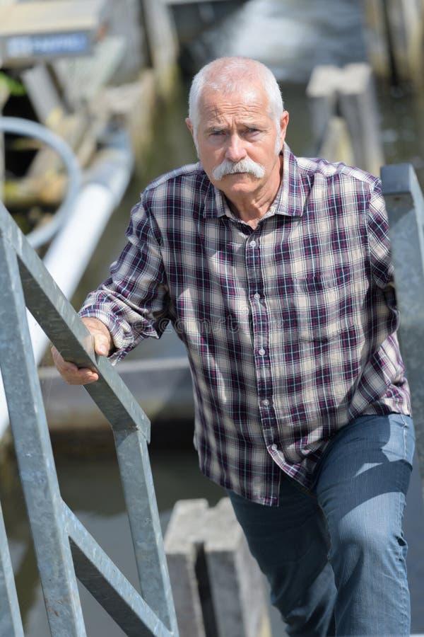 Senior man ascending outdoor staircase stock photography