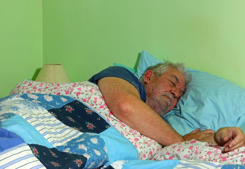 Senior man asleep in bed. stock photography