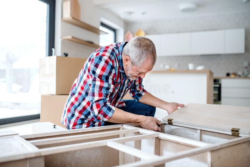 Senior man assembling furniture at home, a new home concept. royalty free stock photos
