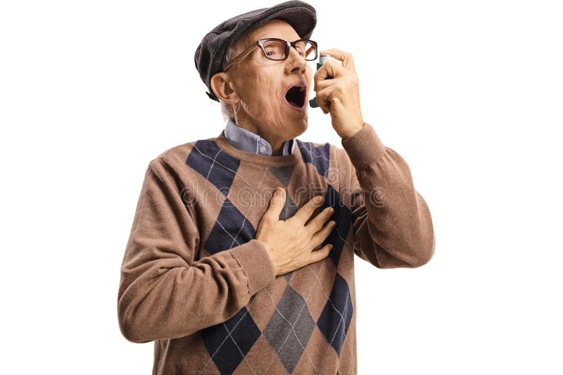 Senior man with asthma using an inhaler royalty free stock images