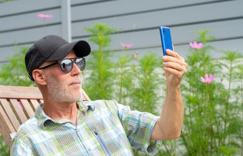Senior man in a baseball cap portrait making selfie royalty free stock image