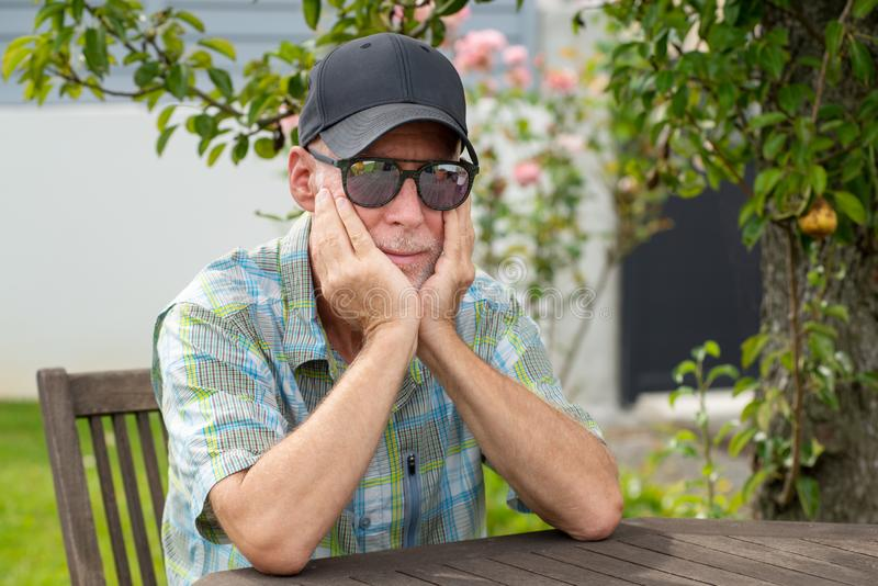 Senior man in baseball cap with sunglasses relaxing in the garden stock photography