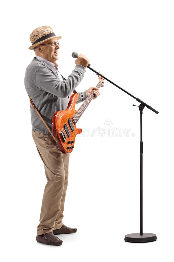 Senior man with a bass guitar singing on a microphone royalty free stock photo
