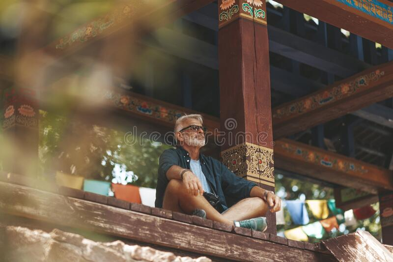 Senior man with beard rest in buddhist monastery. Elderly hiker has active journey. Exotic resort for pensioner royalty free stock photos