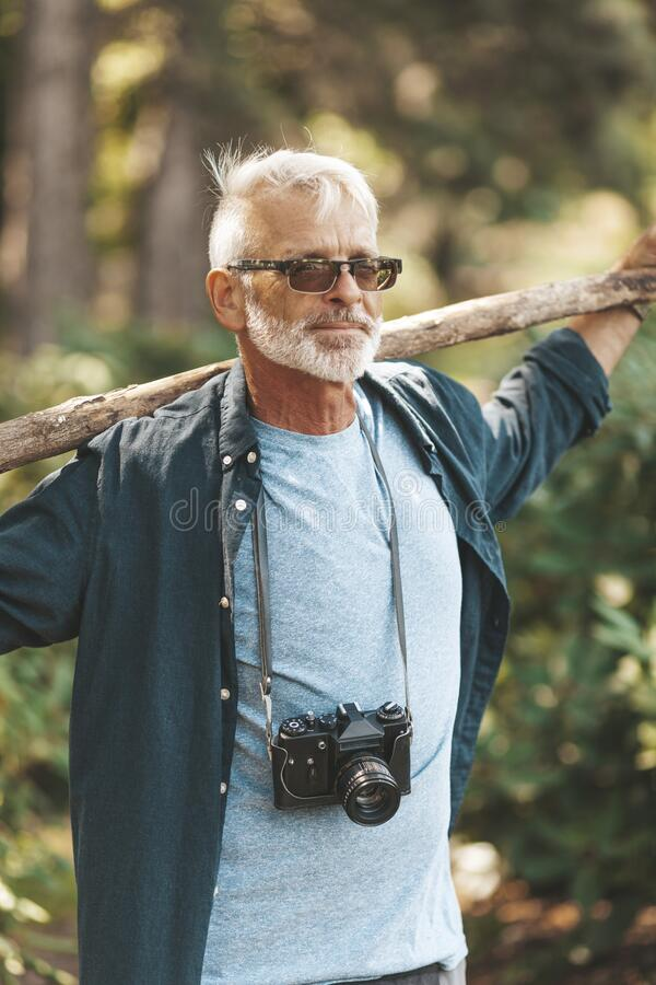 Senior man with beard walks through woods, healthy active lifestyle. Vertical portrait of senior citizen with camera in park royalty free stock photo