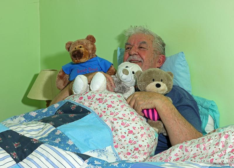 Senior man in bed with soft cuddly toys. A senior man lying in his bed holding soft cuddly toys and smiling royalty free stock photo