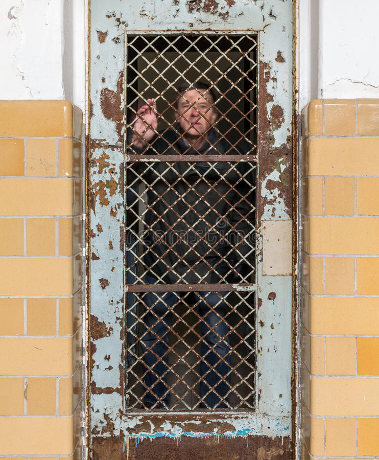 Senior man behind locked barred door in cell. Ghostly senior man behind metal barred door leading to cell and holding onto the bars of the door royalty free stock images