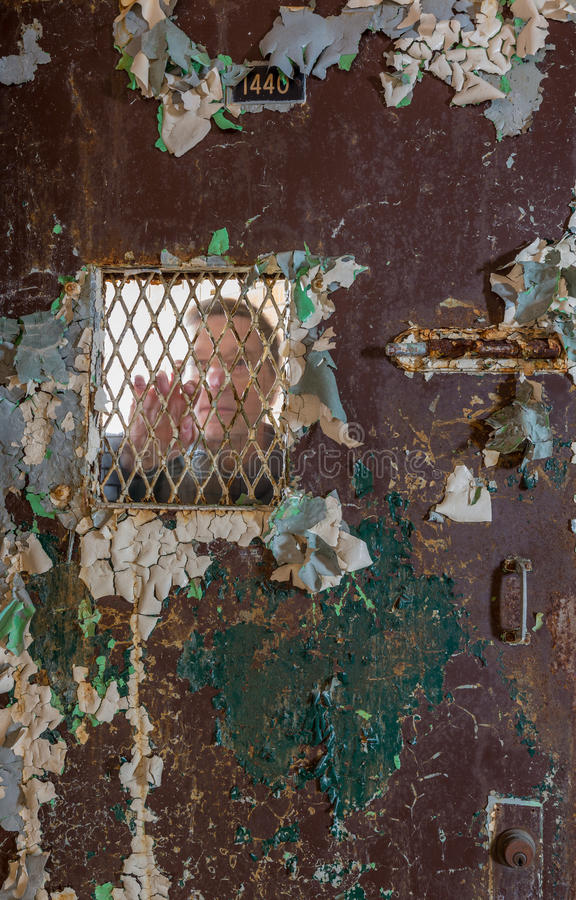 Senior man behind locked barred door in cell. Ghostly senior man behind metal barred door leading to cell and holding onto the bars of the door royalty free stock photo