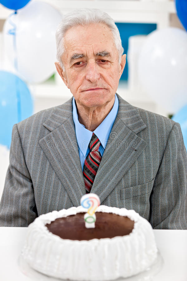 Senior man with birthday cake. Senior man sitting front of birthday cake with candle in the form of questionnaires royalty free stock photo