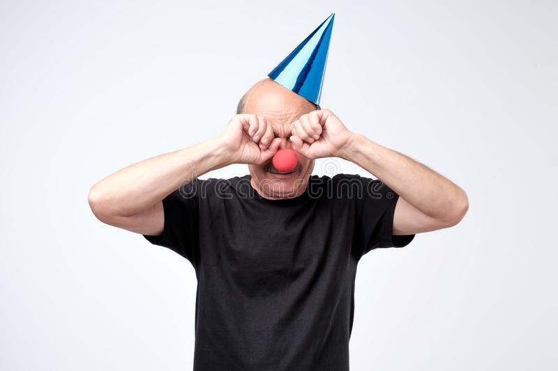 Senior man in birthday cap crying and wiping tears on his party. Dissatisfied disconcerted senior man in birthday cap crying and wiping tears on his party royalty free stock images
