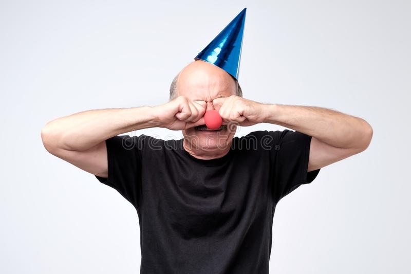 Senior man in birthday cap crying and wiping tears on his party. Dissatisfied disconcerted senior man in birthday cap crying and wiping tears on his party royalty free stock photography