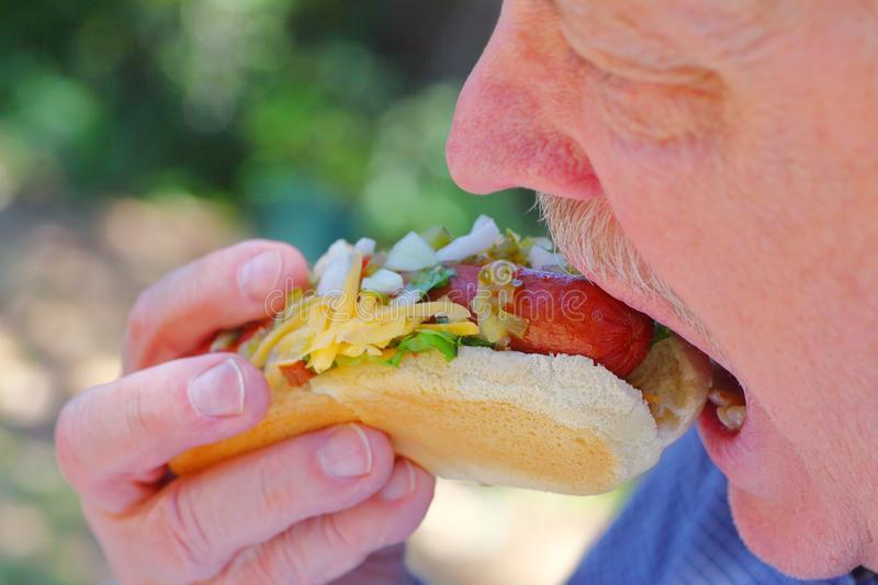 Man eating hot dog with relish and onions. A senior man bites into a hot dog topped with raw onions, relish, lettuce and grated cheese stock photos