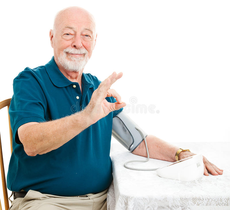 Senior Man - Blood Pressure is A-Okay. Senior man taking his blood pressure at home and getting a good result. Giving Okay hand sign royalty free stock photography