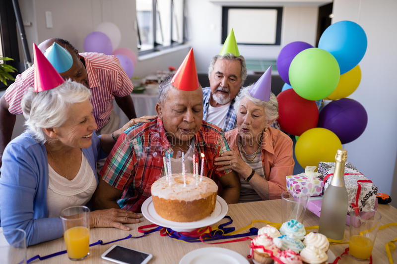 Senior man blowing candles on birthday cake. Senior men blowing candles on birthday cake while enjoying with friends at party stock photos