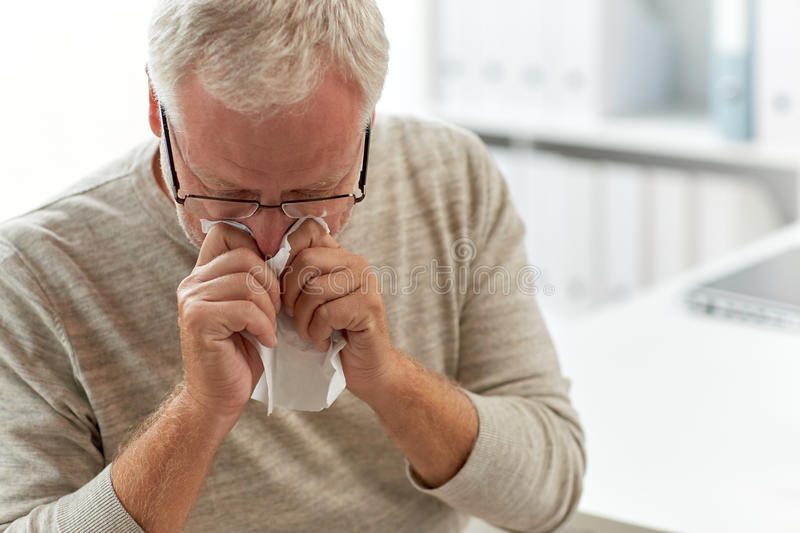 Senior man blowing nose with napkin at hospital. Medicine, healthcare, flu and people concept - senior man blowing nose with napkin at medical office at hospital royalty free stock image