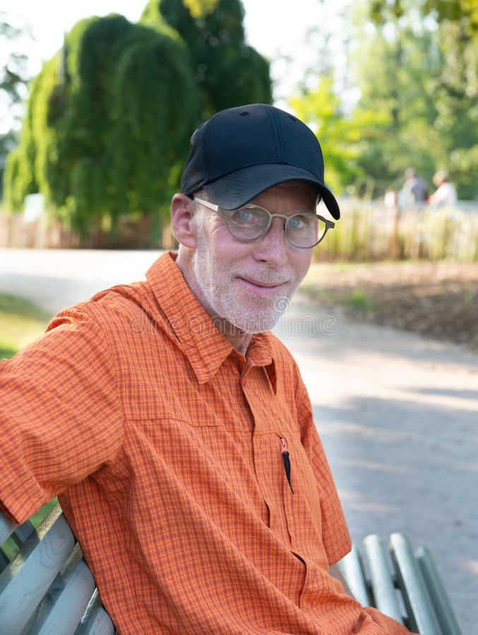 Senior man in blue baseball cap and orange shirt, portrait royalty free stock photo