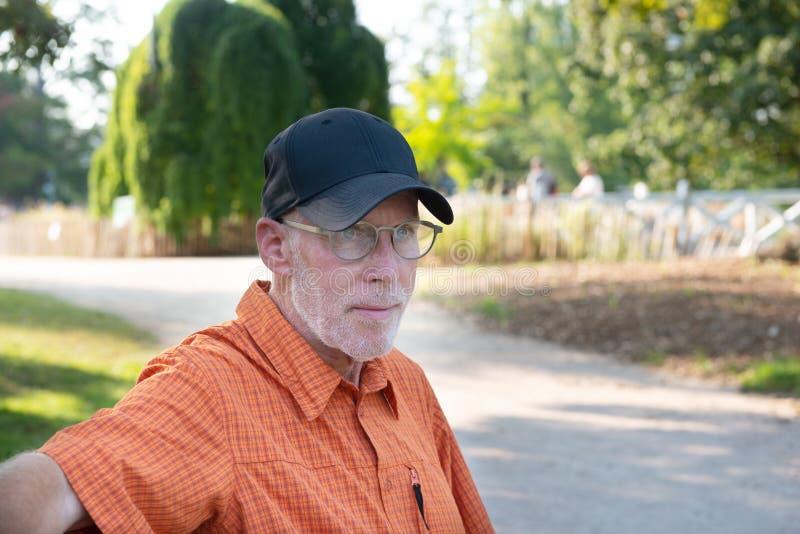 Senior man in blue baseball cap and orange shirt, portrait royalty free stock photos