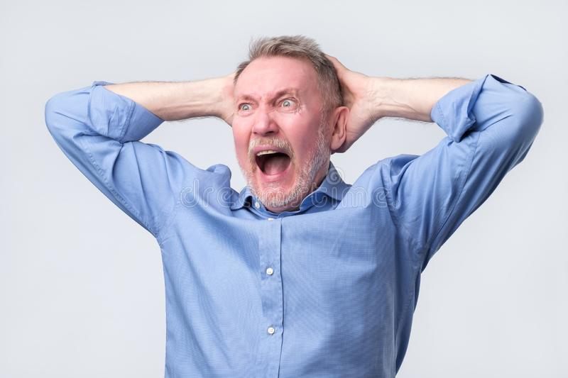 Senior man with angry grimace on his face,with mouth opened in shout. Senior man in blue shirt with angry grimace on his face,with mouth opened in shout, ready royalty free stock photography