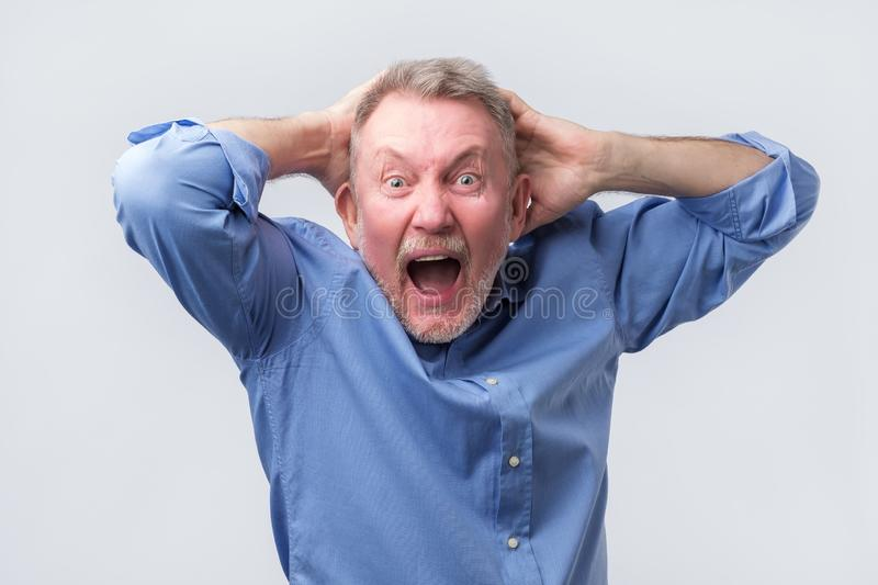 Senior man with angry grimace on his face,with mouth opened in shout. Senior man in blue shirt with angry grimace on his face,with mouth opened in shout, ready royalty free stock image