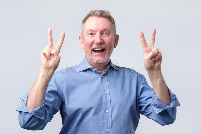 Senior man in blue shirt showing victory sign stock image