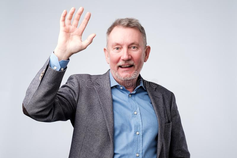 Senior man with blue shirt and suit saying hello. Waving a hand. Welcome home sign stock image
