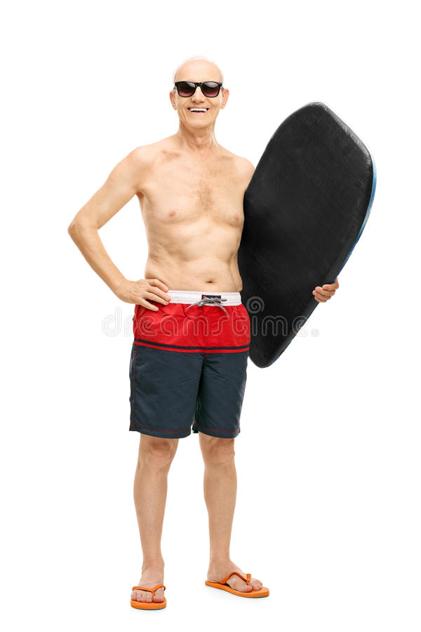 Senior man in blue swim trunks holding a surfboard. Full length portrait of a senior man in blue swim trunks holding a surfboard and looking at the camera royalty free stock photos