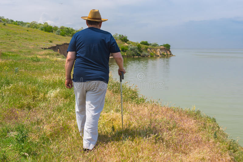 Senior man in blue t-shirt and light pants walking on abrupt riverside of the Dnepr River, Ukraine. Lonely senior man in blue t-shirt and light pants walking on stock photo