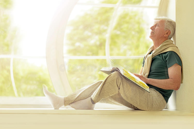 Senior man with book at home stock photography