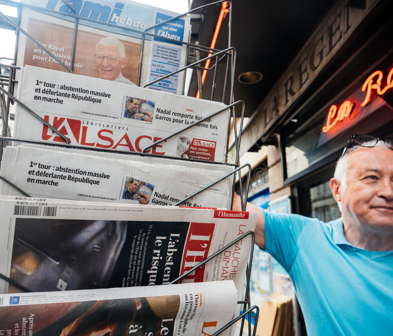 Senior man buying press reactions to French legislative election stock images