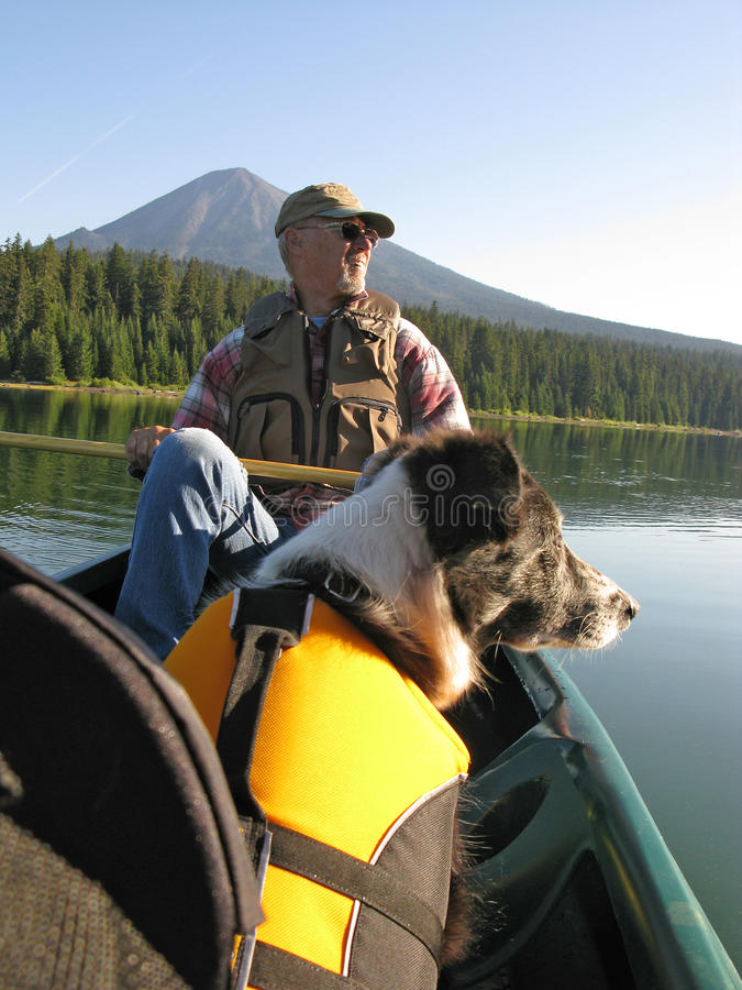 Senior Man canoeing with Dog. Senior Man canoeing with Border Collie Dog on Fish lake, Oregon with Mt. McLaughin in the background stock images